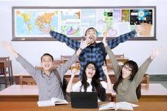 Mani multirazziali di aumento degli studenti nella classe Fotografia Stock