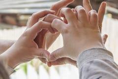 Mani nella figura del cuore Immagine Stock