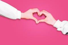 Mani nella forma di cuore isolata su fondo rosa Fotografia Stock