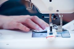 Mani occupate alla macchina per cucire. fotografia stock
