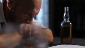 Mani pendenti dell'uomo pensieroso su vetro di whiskey video d archivio