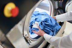 Mani per caricare la lavanderia nella lavatrice Fotografie Stock