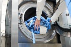 Mani per caricare la lavanderia nella lavatrice Fotografia Stock