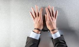 Mani piane anonime dell'uomo d'affari con le manette che aspettano all'ufficio Fotografia Stock