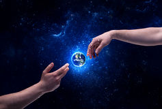 Mani in pianeta Terra commovente dello spazio Immagini Stock