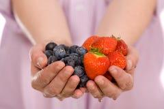 Mani in pieno delle fragole e dei mirtilli Immagine Stock