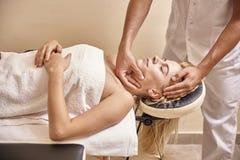 Mani primo piano, testa del fisioterapista del giovane del fronte della donna di massaggio immagine stock