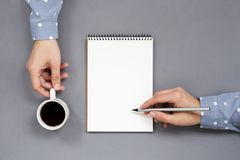 Mani, scrittura e tenuta del ` s della donna sul posto di lavoro minimo grigio Fotografie Stock