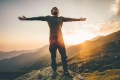 Mani sollevate uomo del viaggiatore alle montagne di tramonto Fotografie Stock Libere da Diritti