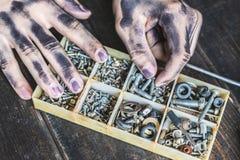 Mani sporche del lavoratore che cercano i bulloni e f matta immagine stock