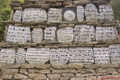 Mani Stones. Buddhist Mani stones inscribed with religious text on a wall in Nepalese Himalaya. Nepal Stock Photo