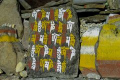 Mani Stones with Buddhist mantra in Himalaya, Nepal. Old Mani Stones inscribed with a Buddhist mantra in the Himalaya region, Nepal. Nepali color letters stock photos