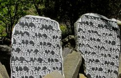 Mani Stones with Buddhist mantra in Himalaya, Nepal. Old Mani Stones inscribed with a Buddhist mantra in the Himalaya region, Nepal. Nepali color letters royalty free stock photography