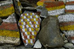 Mani Stones with Buddhist mantra in Himalaya, Nepal. Old Mani Stones inscribed with a Buddhist mantra in the Himalaya region, Nepal. Nepali color letters royalty free stock images