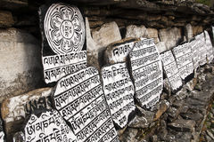 Mani stones. CHAURIKHARKA, NEPAL - CIRCA OCTOBER 2013: Mani stones with the inscription mantra is one of the elements of the Buddhist religion circa October 2013 Royalty Free Stock Images