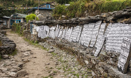 Mani stones. CHAURIKHARKA, NEPAL - CIRCA OCTOBER 2013: Mani stones with the inscription mantra is one of the elements of the Buddhist religion circa October 2013 Royalty Free Stock Photos