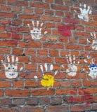 Mani su un muro di mattoni. Immagini Stock