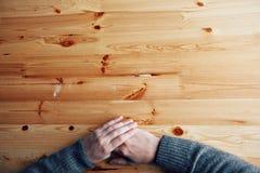 Mani su uno scrittorio di legno in bianco, vista superiore degli uomini allo studio fotografie stock libere da diritti