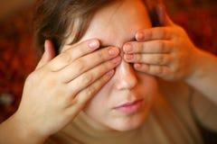 Mani sugli occhi fotografia stock