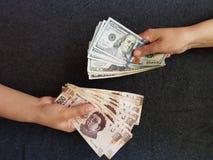 mani sul cambio, sulle fatture messicane e sulle banconote del dollaro Fotografia Stock Libera da Diritti
