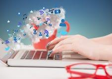 Mani sul computer portatile con le icone e le nuvole che vengono dallo schermo contro il fondo di verde blu Immagini Stock