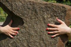 Mani sulla grande roccia Fotografie Stock