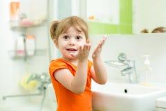 Mani sveglie di lavaggio della bambina in bagno fotografia stock libera da diritti