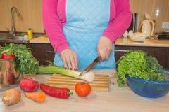 Mani umane che cucinano l'insalata delle verdure in cucina sulla tavola Concetto sano del pasto Fotografia Stock