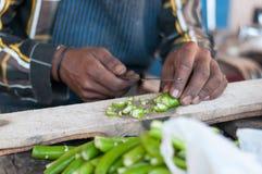 Mani umane che cucinano le verdure in cucina Fotografia Stock Libera da Diritti