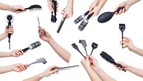 Mani umane che giudicano gli strumenti di lavoro di parrucchiere isolati su bianco Fotografia Stock