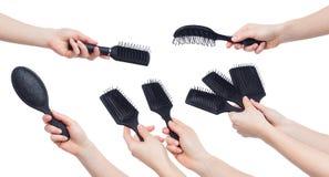 Mani umane che giudicano le varie spazzole isolate su bianco Fotografie Stock Libere da Diritti