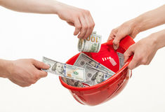 Mani umane che mettono i dollari in un casco rosso Immagine Stock