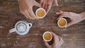 Mani umane che prendono le tazze di tè dalla Tabella rustica di legno e che bevono vista di cerimonia di tè verde del cinese trad archivi video