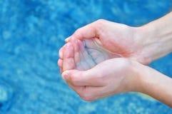 Mani umane che spruzzano acqua pura Fotografia Stock Libera da Diritti