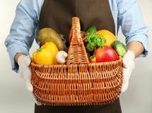 Mani umane che tengono canestro di vimini con differenti frutta e verdure Fotografia Stock Libera da Diritti