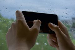 Mani umane che tengono il telefono e che giocano sul touch screen con i vostri pollici sui precedenti della natura e del cielo bl fotografia stock libera da diritti