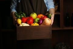 Mani umane che tengono scatola di legno con i frutti differenti Immagini Stock Libere da Diritti