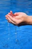 Mani umane con chiara acqua sui precedenti blu Immagine Stock