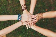 Mani unite delle amiche primo piano, ragazze in braccialetti di boho Immagini Stock Libere da Diritti