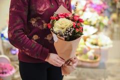 Mani variopinte del commesso dei fiori del mazzo della tenuta del fiorista Immagine Stock Libera da Diritti