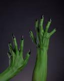 Mani verdi della strega con i chiodi neri che allungano su, body art reale Fotografia Stock