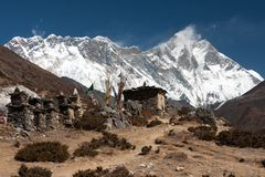 Mani walls along the trail to Pangboche. Mani wall and prayer flags along the trail to to Pangboche with summit of Mt. Everest above Nuptse to Lhotse ridge in Stock Image