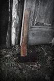 Maniac axe in blood by the grunge door Stock Photos