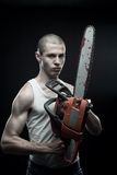 Maniac with chainsaw. Horrible maniac holding bloody chainsaw over dark background royalty free stock image