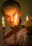Maniac With Knife. Portrait of man with knife in the candles light representing a funny evil character Stock Photography