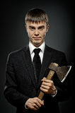 Maniac. Portrait  man in black costume and black necktie with axe, sinister look Stock Image