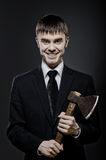Maniac. Portrait  man  in black costume and black necktie with axe, sinister look and smile Stock Images