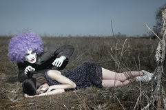 Maniac and victim. Sleeping girl outdoors and crazy maniac clown touching her shirt. Artistic colors added Royalty Free Stock Images