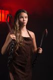 Maniac woman with hooks. In hand on grid background Royalty Free Stock Photo