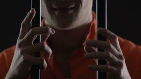 Maniaco loco que sostiene barras de la célula del metal y smirking en la cámara, pena de muerte metrajes